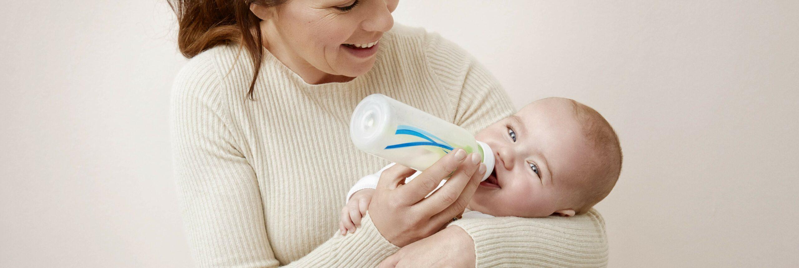Vrouw die baby fles geeft