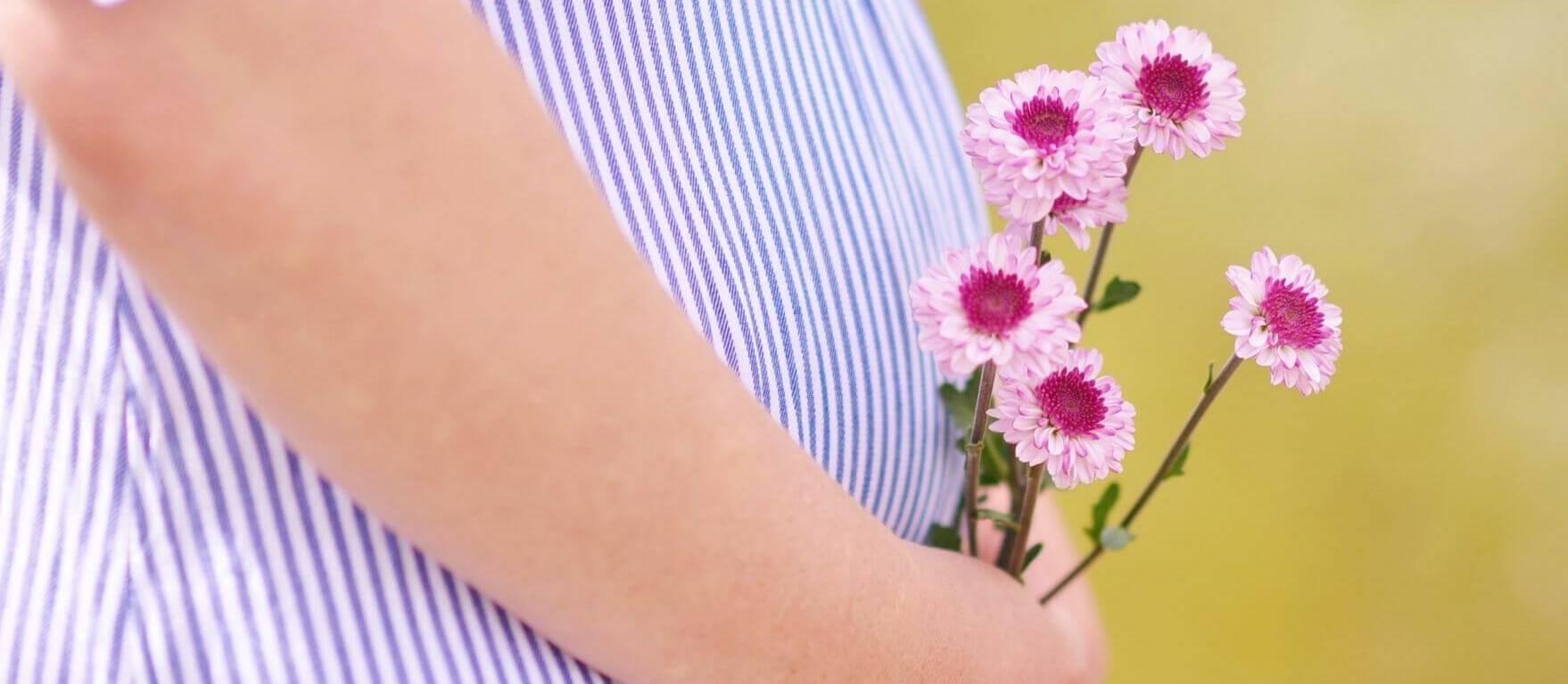 Zwangere vrouw houdt bloemen vast