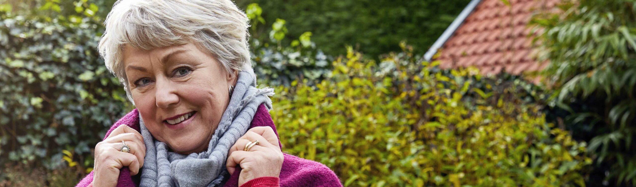 Vrouw met grijs haar in tuin