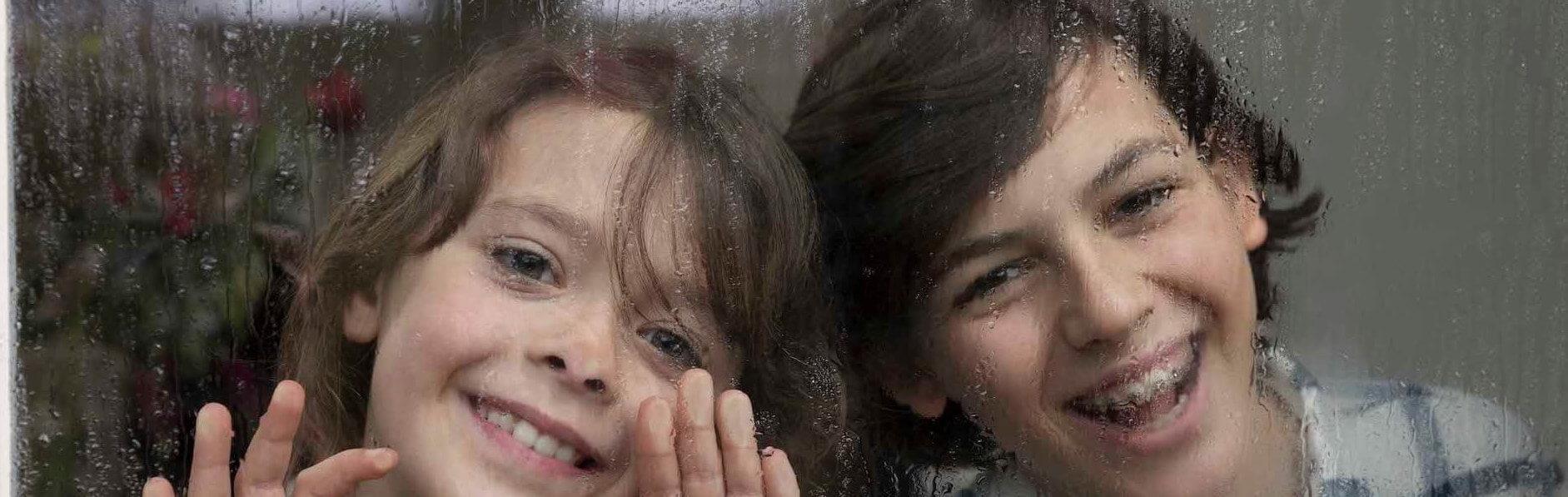 Kinderen achter een nat raam