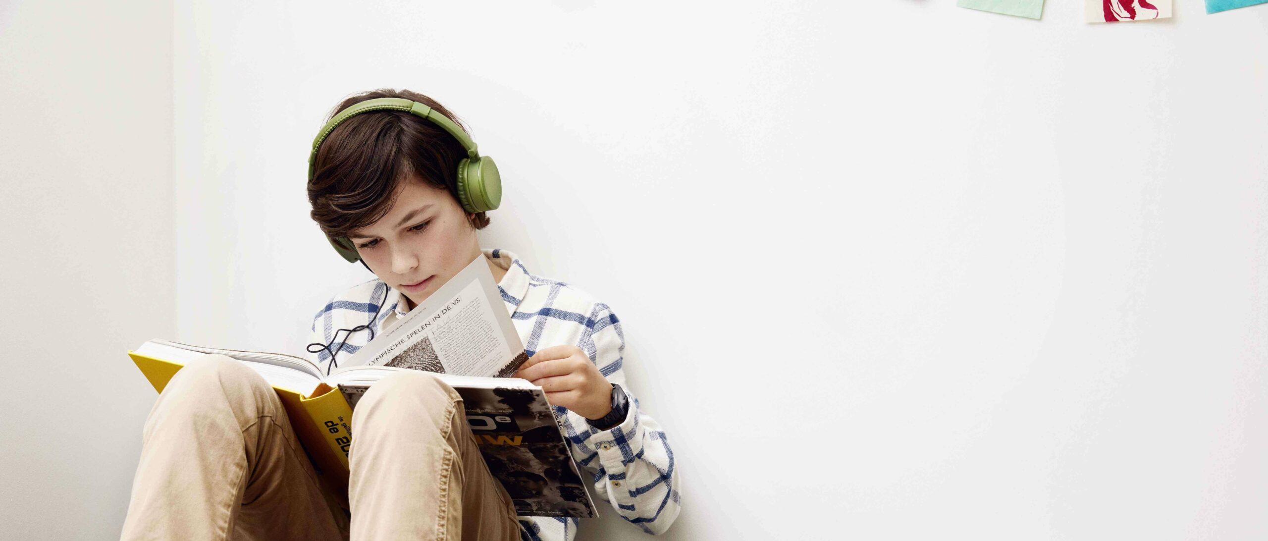 Lezende jongen met koptelefoon